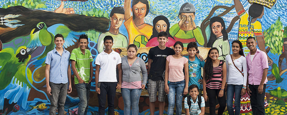 a group of teenagers standing in front of a mural painting