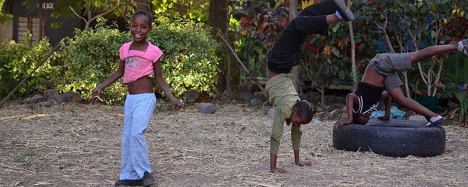 Drei Kinder betätigen sich akrobatisch auf einem grünen Hof.