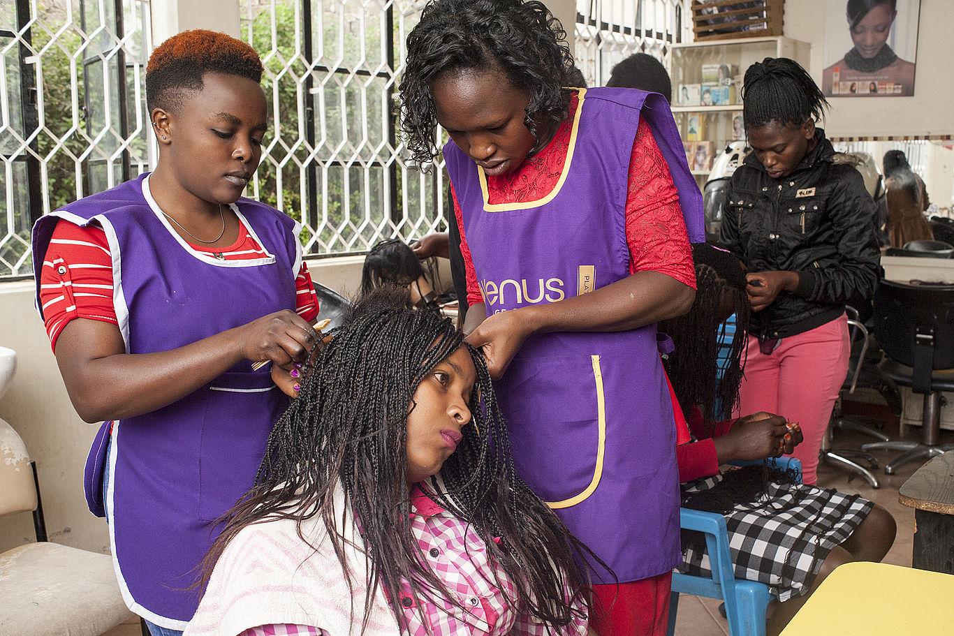 Zwei junge Frauen stehen in einem Friseursalon und frisieren eine dritte Frau.