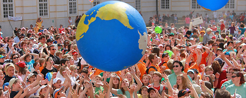 a big group of people playing with an inflatable globe